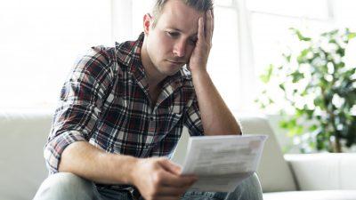 בחור תופס את הראש שמביט בכל הבלאגן שיש לו בתשלומי ביטוח היקרים לכן מחליט לעשות סדר בביטוחים