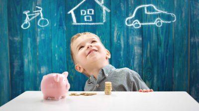 ילד בן שלוש יושב על השולחן עם כסף וקופת חיסכון בצורת חזירון. ילד שמח עם מטבעות. ילד שחולם על הבית ועל רכב ואופניים